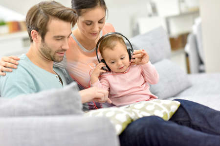 watching movie: Couple with baby  in sofa watching movie on tablet