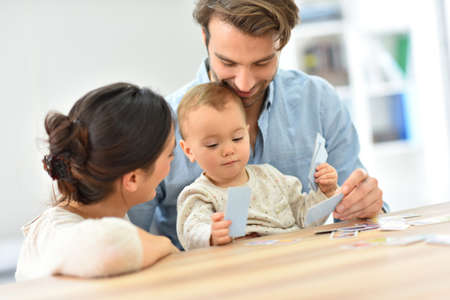 family playing: Parents with baby girl playing cards Stock Photo