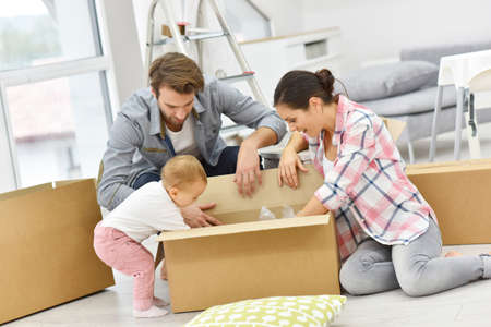 cardboard: Young family unpacking boxes in new home Stock Photo