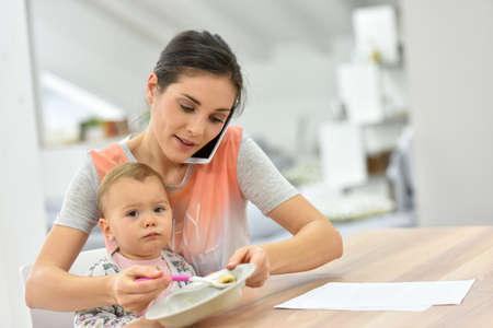 Bezige moeder aan de telefoon voeden baby Een tegelijk