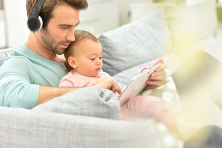 using tablet: Daddy and baby girl in sofa using tablet and headphones Stock Photo