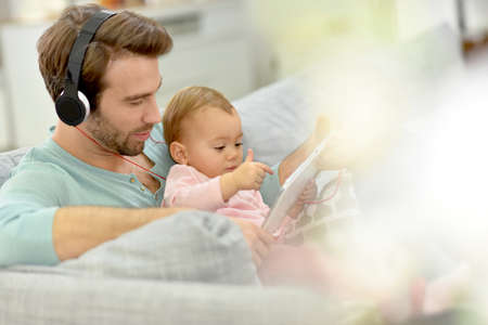 baby girl: Daddy and baby girl in sofa using tablet and headphones Stock Photo
