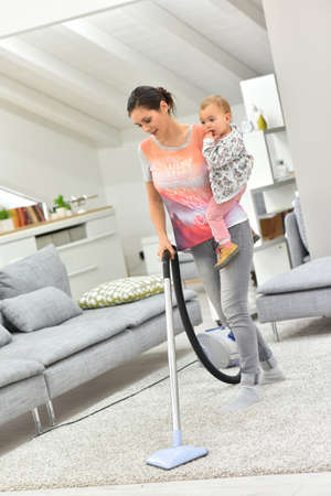 girl  care: Mother vaccum cleaning floor with baby in arms Stock Photo