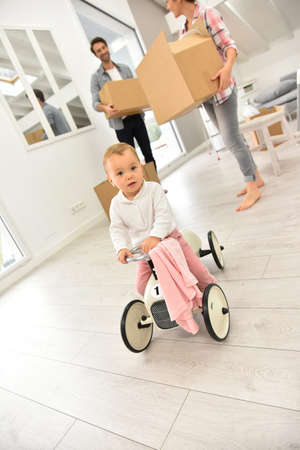 3 persons: Baby girl playing with child car while family moving in