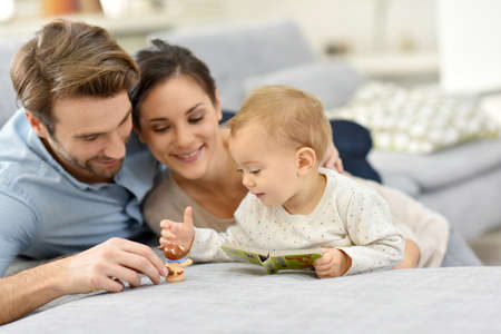 woman on couch: Parents enjoying playing with baby girl