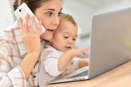 Besetzt junge Unternehmerin auf Laptop, Baby auf Schoß