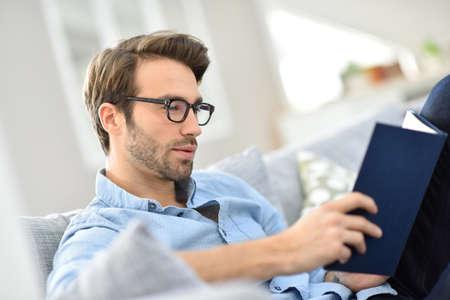 소파에 책을 읽고 안경을 가진 남자