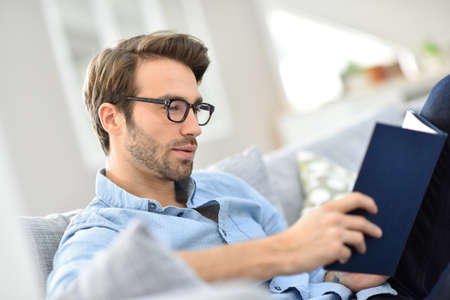 Man with eyeglasses reading book in sofa