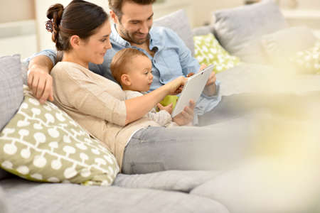 baby girl: Parents with baby girl in sofa using digital tablet