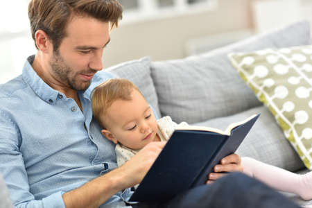 quiet adult: Father and child reading book in sofa