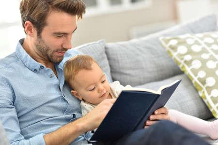 papa: P�re et enfant lisant un livre dans le canap�