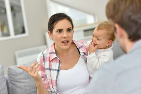people arguing: Man and woman arguing in front of baby Stock Photo