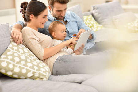 family playing: Parents with baby girl in sofa using digital tablet
