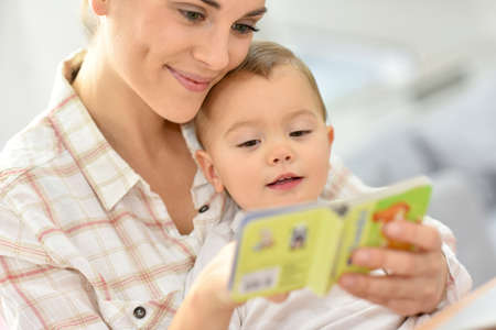 Sweet moment with mother reading book to baby Stock Photo