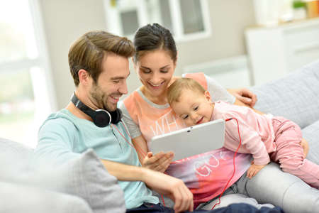 woman tablet: Couple with baby  in sofa watching movie on tablet