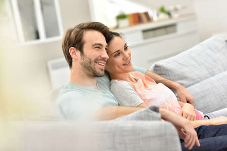relaxed woman: Couple relaxing in sofa and watching tv Stock Photo