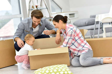 Young family unpacking boxes in new home Stock Photo