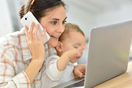 madre trabajadora: joven empresaria ocupado trabajando en la computadora portátil, bebé en el regazo