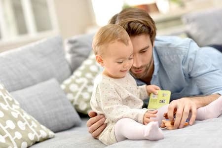 family with baby: Daddy playing wih baby girl on sofa Stock Photo