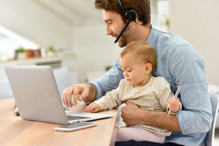 Busy businessman working from home and watching baby Stock Photo