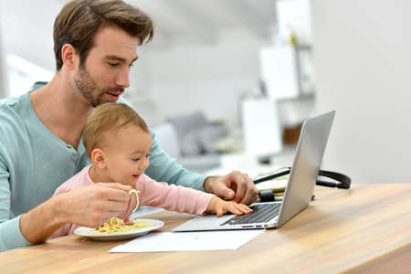 homeoffice: Man working from home and feeding baby