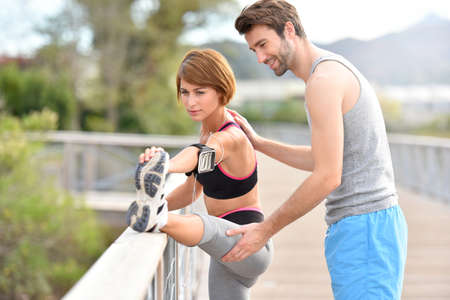stretch out: Coach with athletic girl exercising outside