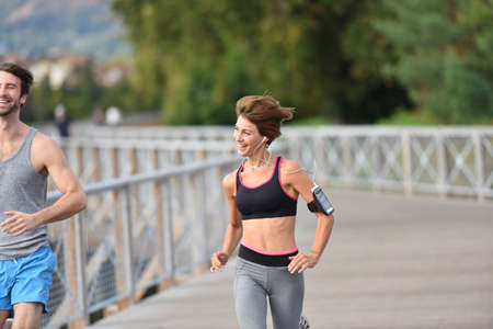 joggers: Couple of joggers running on bridge Stock Photo