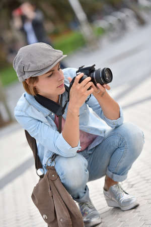 knelt: Woman reporter on a shooting day in urban area Stock Photo