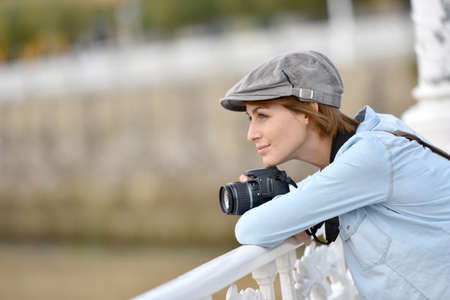 admiring: Young woman with photo camera admiring scenery over bridge Stock Photo
