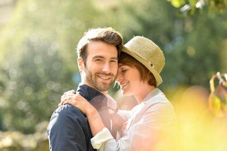 pareja abrazada: Joven pareja de enamorados que abrazan en parque Foto de archivo