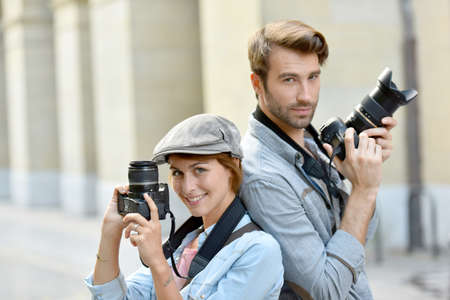 newsman: Trendy photographers with camera standing in the street