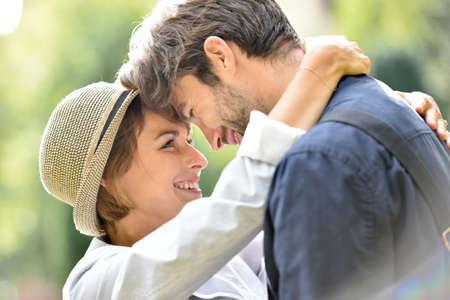 Joven pareja romántica abrazados en el parque, la luz del sol