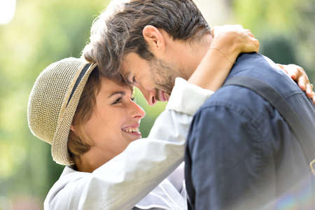 sweet smile: Romantic young couple embracing in park, sunlight Stock Photo