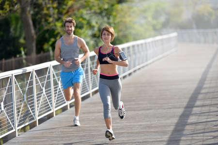 fitness woman: Couple running on riverside Stock Photo