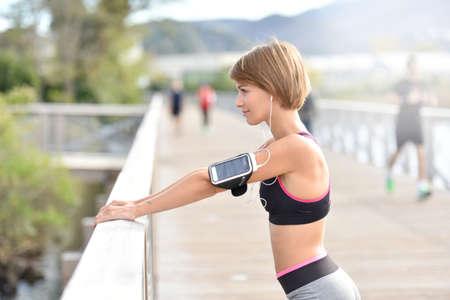 estiramiento: Mujer que estira hacia fuera después de correr Foto de archivo