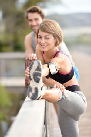 WOMAN FITNESS: Athletic couple stretching out after running