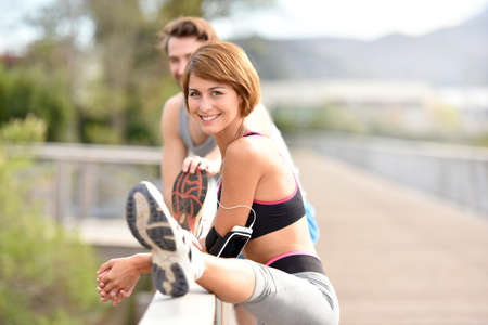 stretch out: Athletic couple stretching out after running