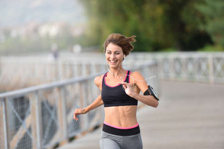 sport woman: Cheerful athletic girl running outside