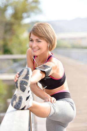 WOMAN FITNESS: Woman stretching out after running Stock Photo