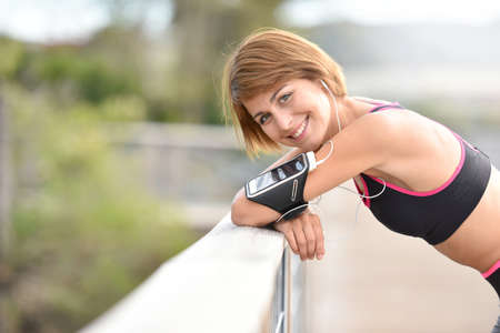 stretch out: Portrait of cheerful woman in running outfit