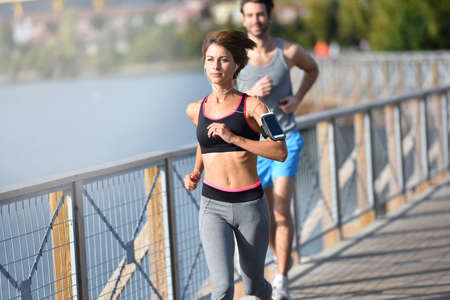 fit woman: Couple running on riverside Stock Photo