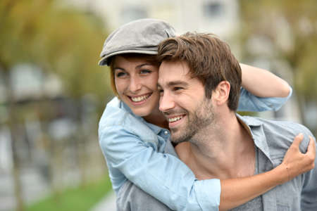 loving couples: Portrait of man giving piggyback ride to girlfriend Stock Photo