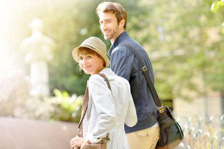boyfriend: Happy young woman walking in park, holding boyfriends hand
