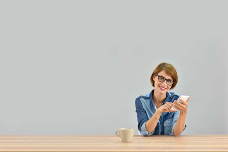 25 years old: Young woman sitting at desk sending message on smartphone