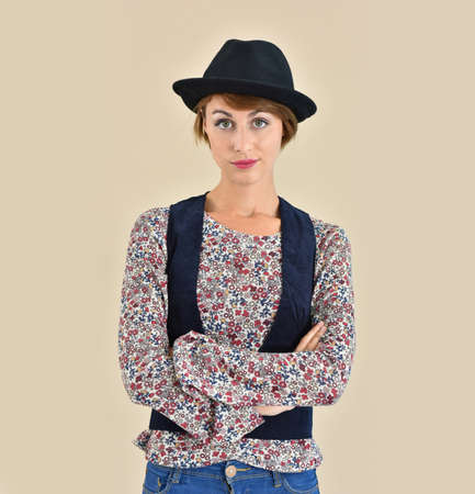 girl in a hat: Cheerful trendy girl with hat standing on beige background