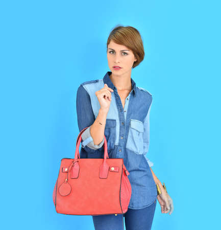red purse: Attractive young woman on blue background holding red purse