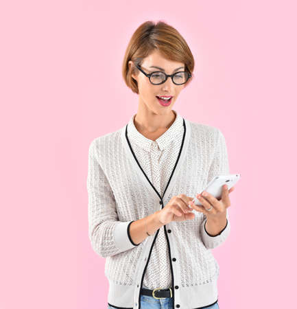 publicity: trendy girl with eyeglasses using smartphone, pink background