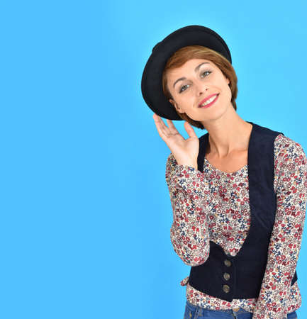 25 years old: Trendy girl with black hat standing on blue background Stock Photo
