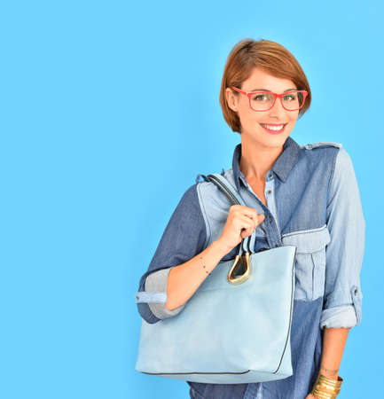 red purse: Atractive city girl with red glasses, isolated on blue background