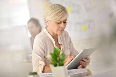 workteam: Senior businesswoman in office working on digital tablet